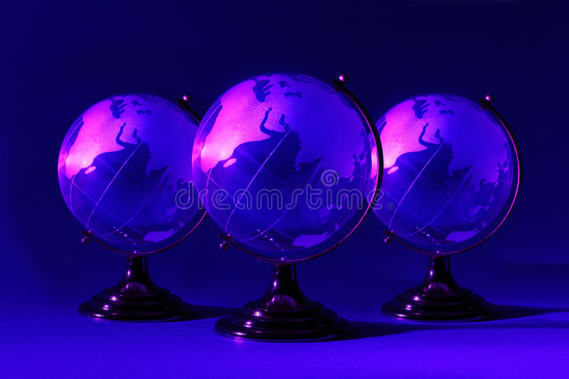 Three glass globes at stand is illuminated by pink. Three small blue glass globes at stand is illuminated by pink light; Africa and Eurasia stock image