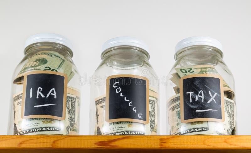 Three glass jars on wooden shelf for savings stock photo
