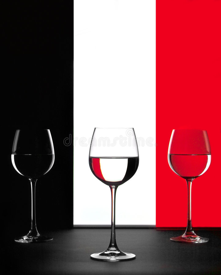 Three glasses. Three vine glasses with red and black reflections stock photography