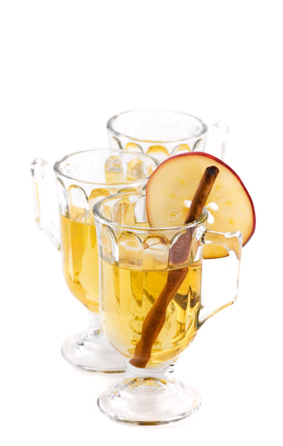 Three Glasses of Apple Cider. Line of glasses of apple cider - front glass contains cinnamon stick and apple slice on rim stock images