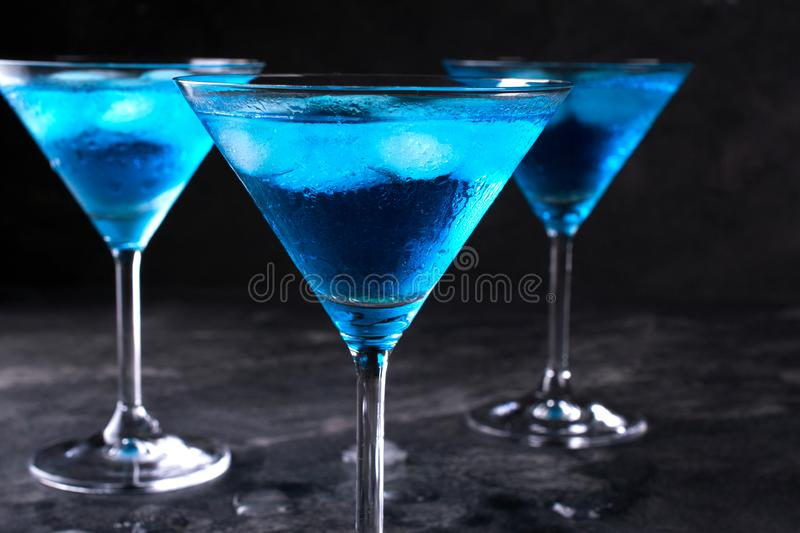 Three glasses of blue cold martini cocktail with ice and clear dew drops on glass on a gray background , closeup shot royalty free stock image