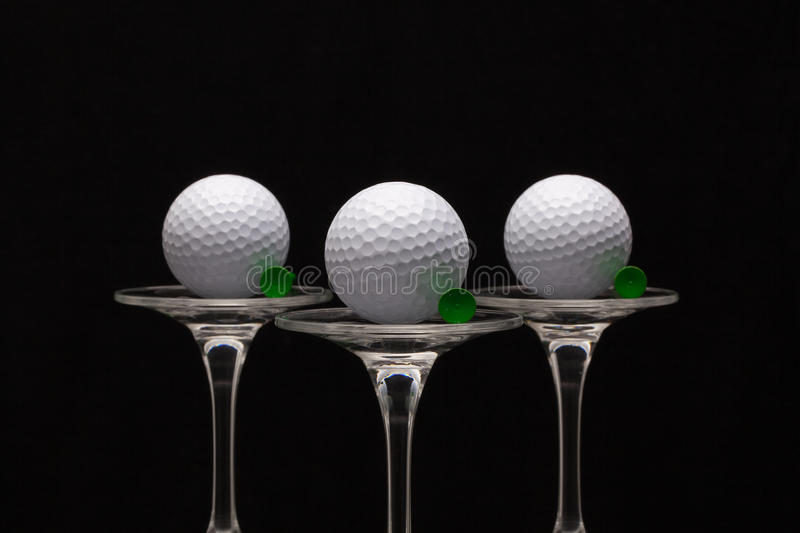 Three glasses of champagne and golf balls. Three glasses of champagne with golf balls royalty free stock image