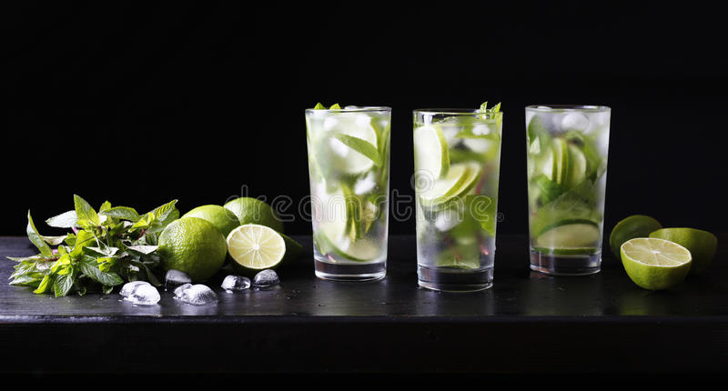 Three glasses of cocktail mojito lemonade on the bar. Party cocktail. Lime, ice and mint on the table. Black background. stock photography