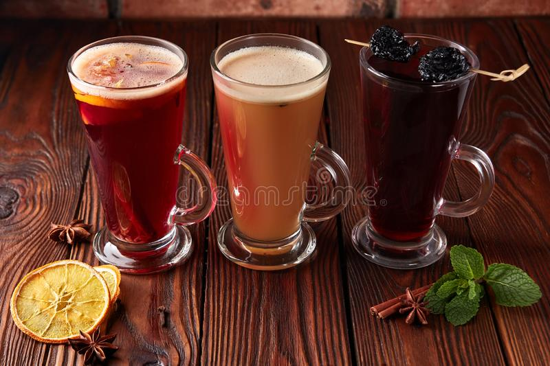 Three glasses with hot alcoholic drinks. Mulled wine, punch and apple cider cocktail with orange, cinnamon, cloves and star anise on dark wooden table stock images
