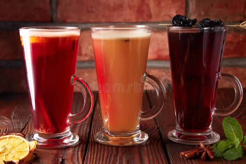 Three glasses with hot alcoholic drinks. Mulled wine, punch and apple cider cocktail with orange, cinnamon, cloves and star anise on dark wooden table stock photos