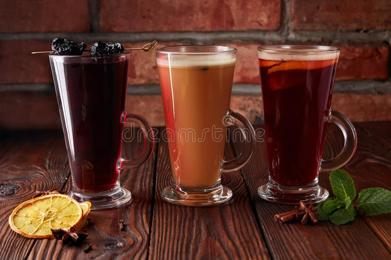 Three glasses with hot alcoholic drinks. Mulled wine, punch and apple cider cocktail with orange, cinnamon, cloves and star anise on dark wooden table royalty free stock images