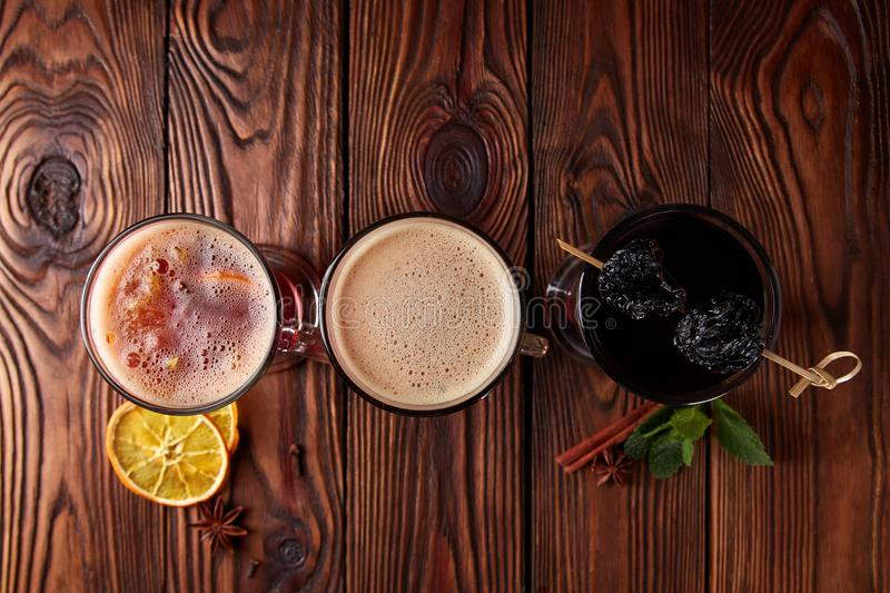 Three glasses with hot alcoholic drinks. Mulled wine, punch and apple cider cocktail with orange, cinnamon, cloves and star anise on dark wooden table, view stock images