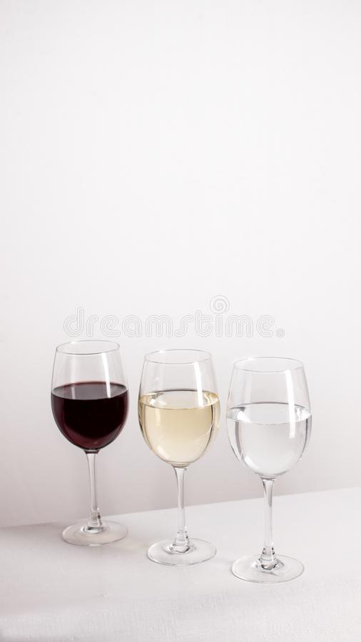 Three glasses of red, white wine and water standing in one line on grey background. royalty free stock photo