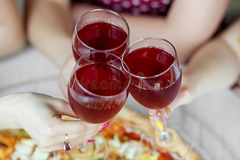 Three glasses of red wine in female hands. Toast at a party. Concept of alcohol, holiday royalty free stock image