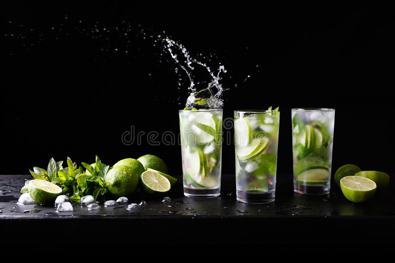 Three glasses of refreshing Mojito rum alcohol cocktail on the bar, splashes in a glass. Party cocktail. Lime, ice and royalty free stock photo