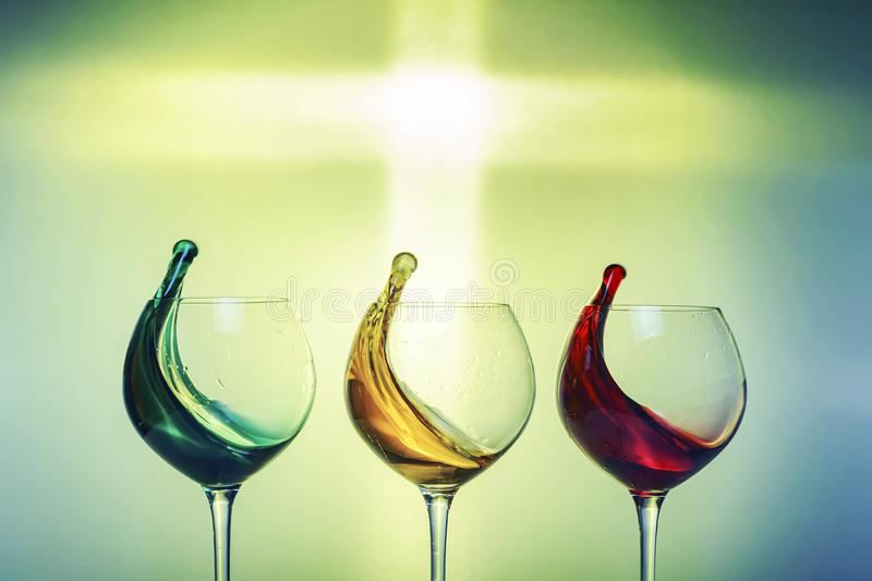 Three glasses with splashes of colorful drinks on a colorful festive background. royalty free stock images