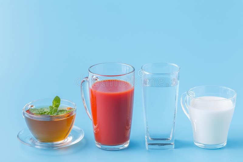 Three glasses with water, milk and juice closeup royalty free stock photo