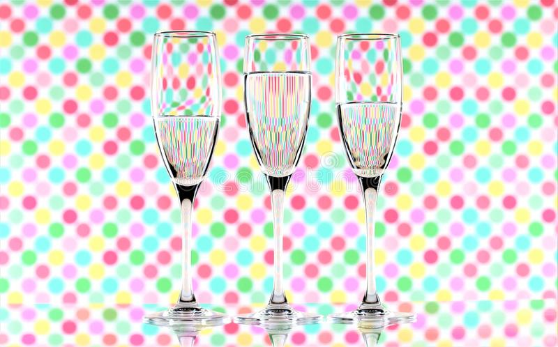 Three glasses of water on a multicoloured background showing refraction. Canvas wall art. Three tall glasses of water on a multicoloured background showing stock photography