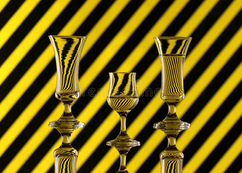 Three glasses of water on a multicoloured background showing refraction. Canvas wall art. Three glasses of water on a yellow and black striped multicoloured stock photos