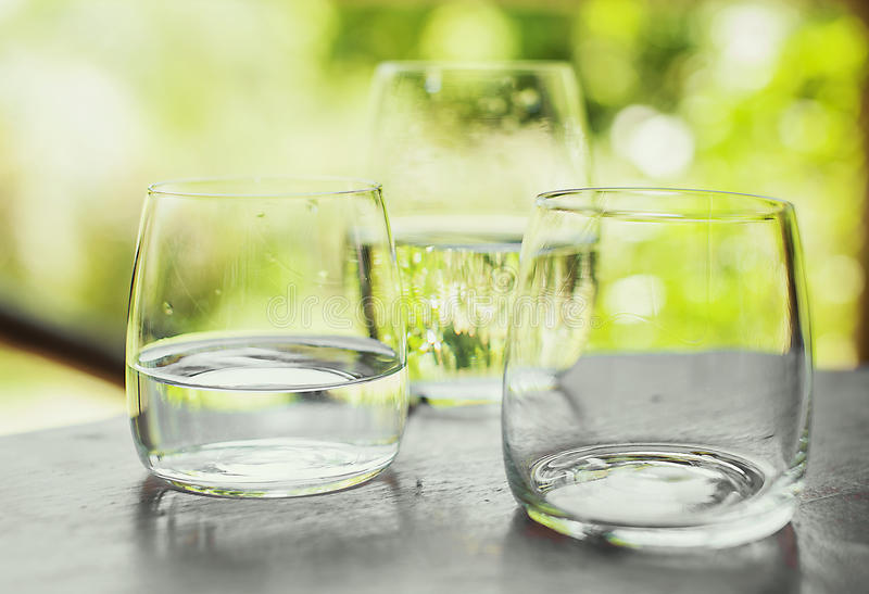 Three glasses of water on nature background. Three glasses on the table: two with water and one empty on nature background. Healthy, diet and detox concept royalty free stock photo