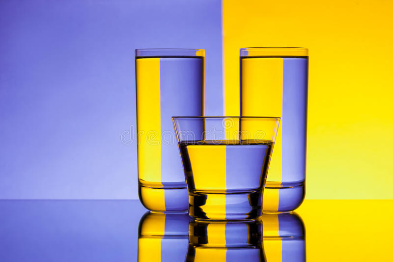 Three glasses with water over purple and yellow background. Copy space royalty free stock photos