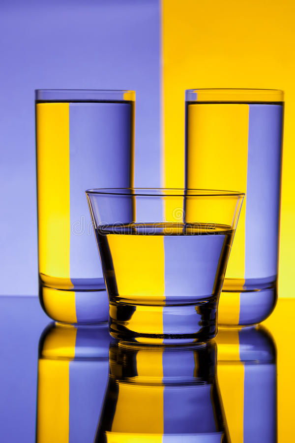 Three glasses with water over purple and yellow background. Copy space royalty free stock photography
