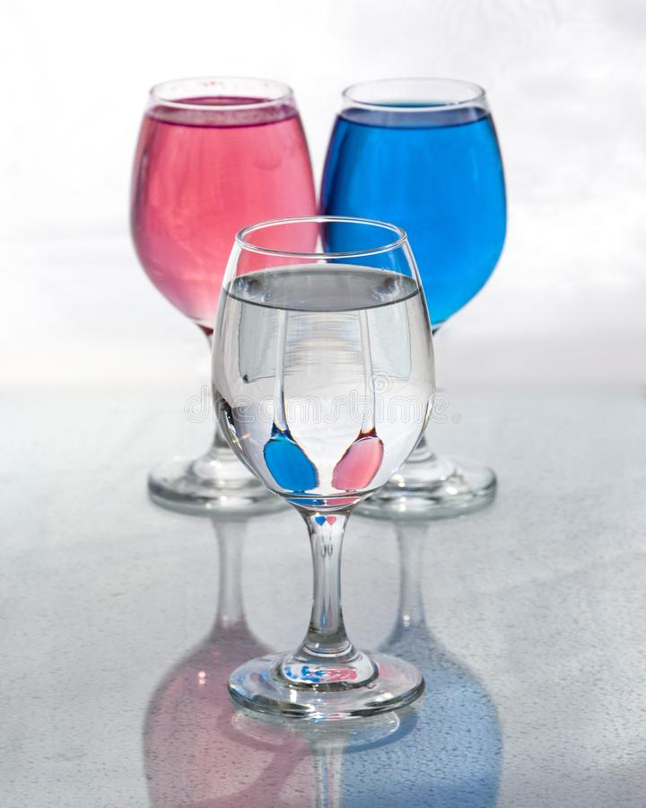 Three glasses of water showing reflections with distortions stock images