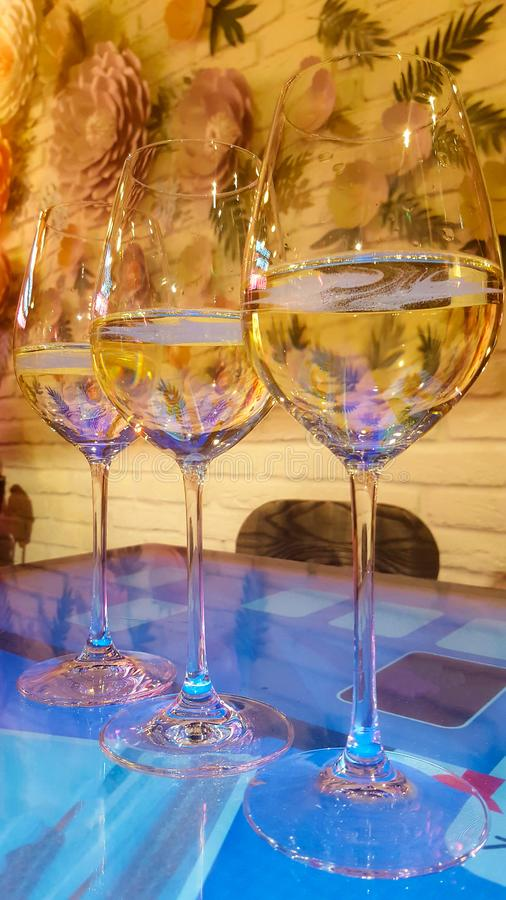 Three glasses of white wine with some residual effervescent bubbles out-gassing on table in bar. Vertical. Alcohol, background, beverage, drink, liquid royalty free stock photography