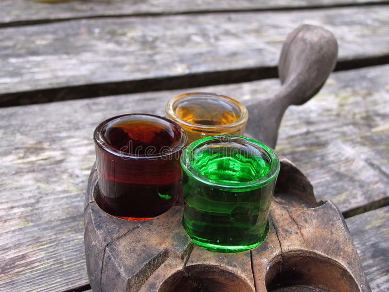 Three glasses on a wooden tray. Three glasses of different liquere on a wooden tray. Green, yellow and dark red stock photos