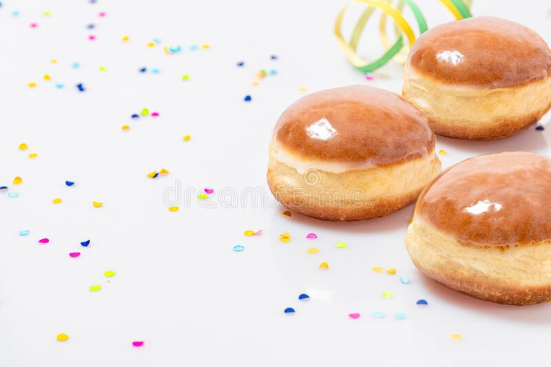 Three Glazed doughnuts with konfetti and streamers royalty free stock photo