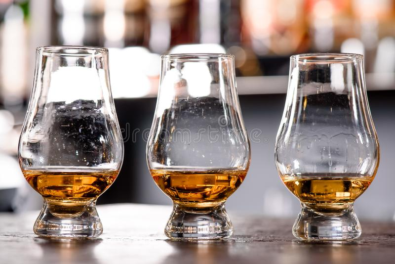 Three Glencairn Glass with whiskey on a bar wooden counter close up on the background of blurry bottles royalty free stock photos
