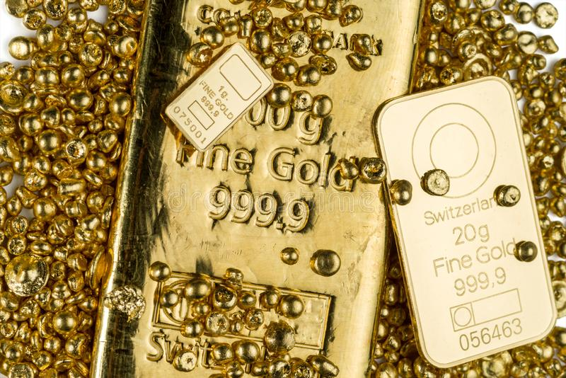 Three gold bars of different weights lie in a pile of gold granules. stock images