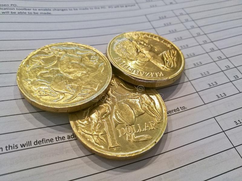 Three gold coins of Australian dollars on invoice sheet royalty free stock photography