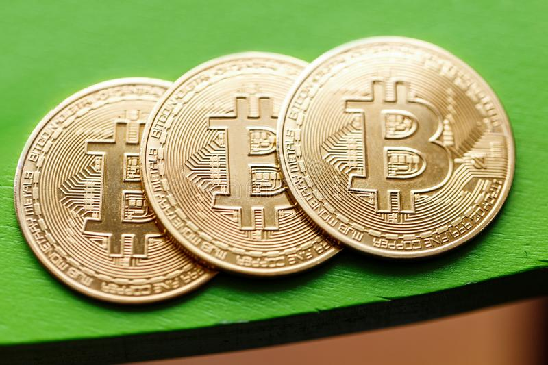 Three gold coins bitcoin on a green background royalty free stock photo