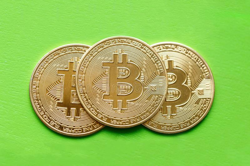 Three gold coins bitcoin on a green background stock image