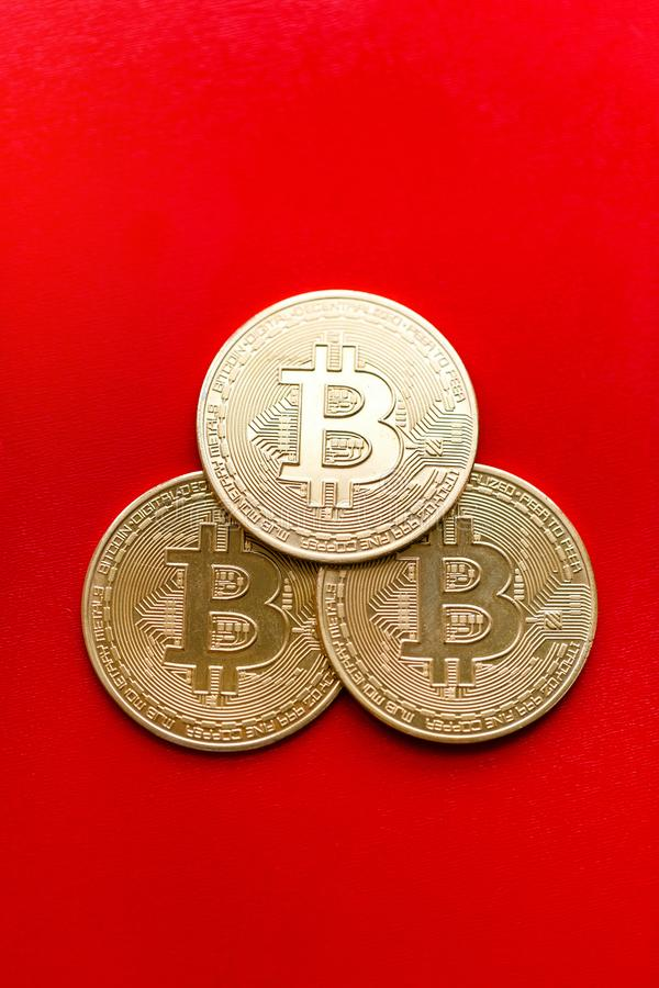 Three gold coins bitcoin on a red background stock image