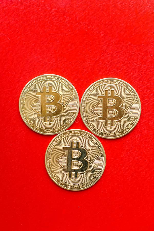 Three gold coins bitcoin on a red background royalty free stock photo