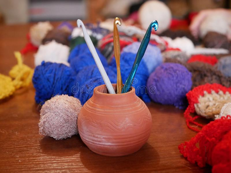 Three gold, green and white crochet hooks in a ceramic vase against a background of several multicolored balls of woolen thread on royalty free stock photography