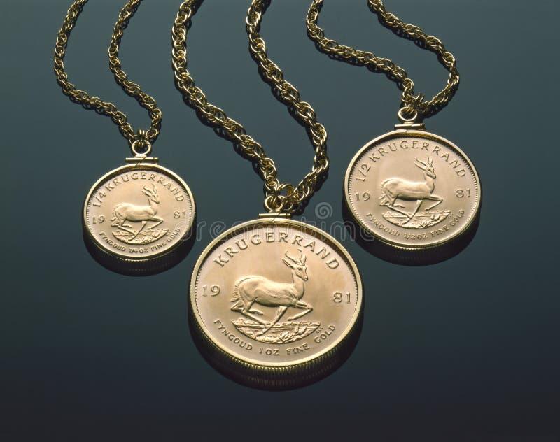 Three Gold Krugerrand Necklaces On Black Plexiglass stock images