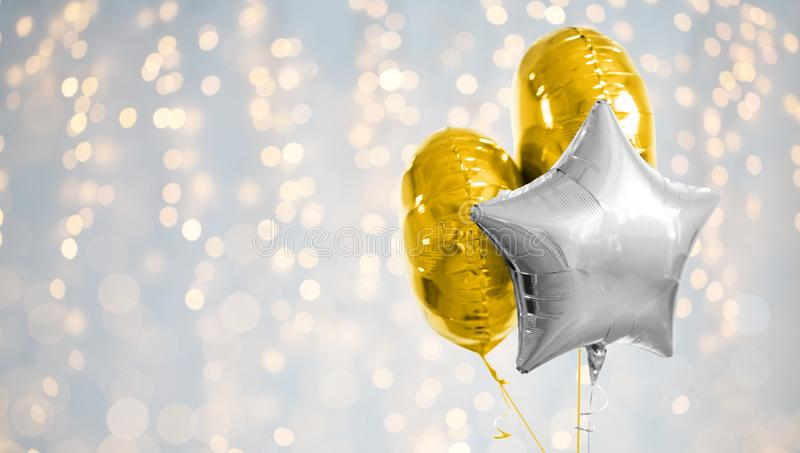 Three gold and silver helium balloons on white. Holidays and birthday party decoration concept - three metallic gold and silver helium balloons of different stock images