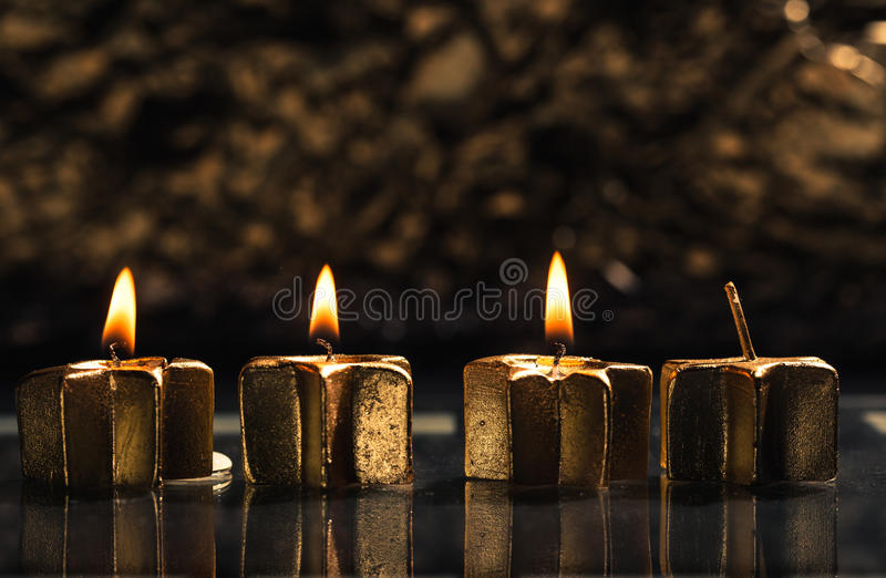 Three golden advent candles lit with bokeh background. Three golden candles lit for third advent, shallow depth of field with reflection and bokeh light royalty free stock image