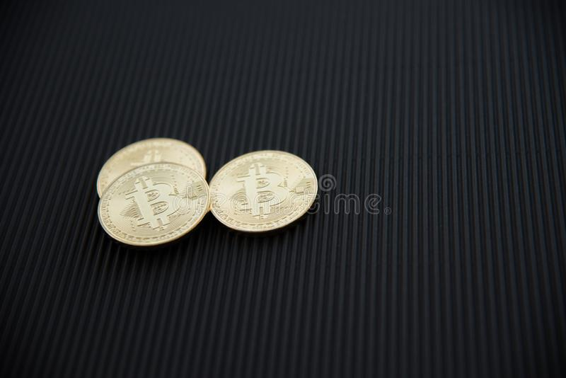 Three golden Bitcoin overlapping on black surface stock images