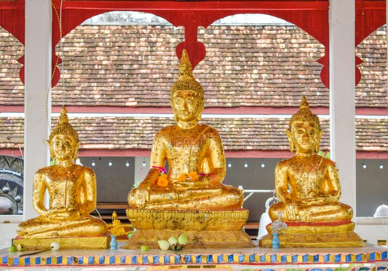 Three golden Buddha statues at the base royalty free stock photo