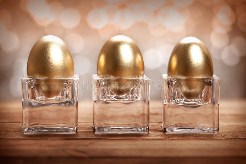 Three golden eggs. On brown background stock photo
