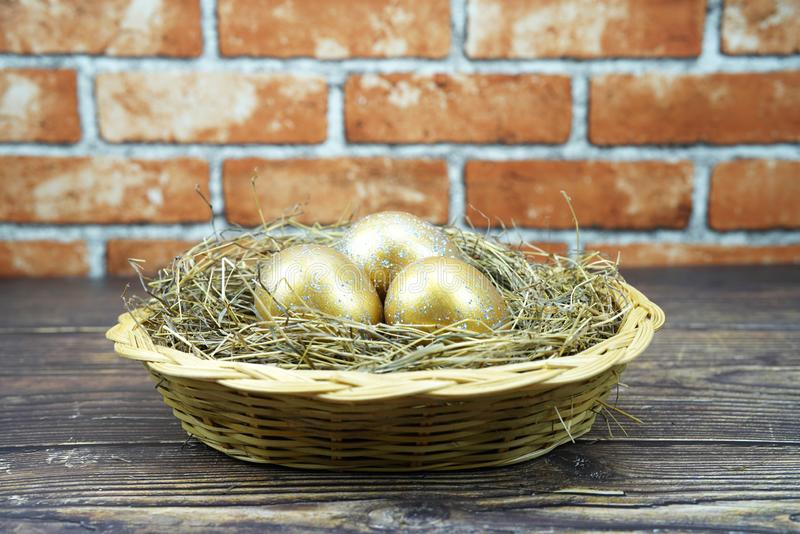 Three golden eggs in the basket stock photography