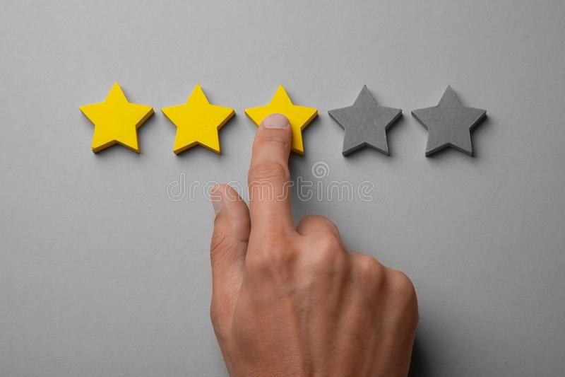 Three golden yellow stars out of five. Man points finger at the star, puts rating. Recalls royalty free stock images