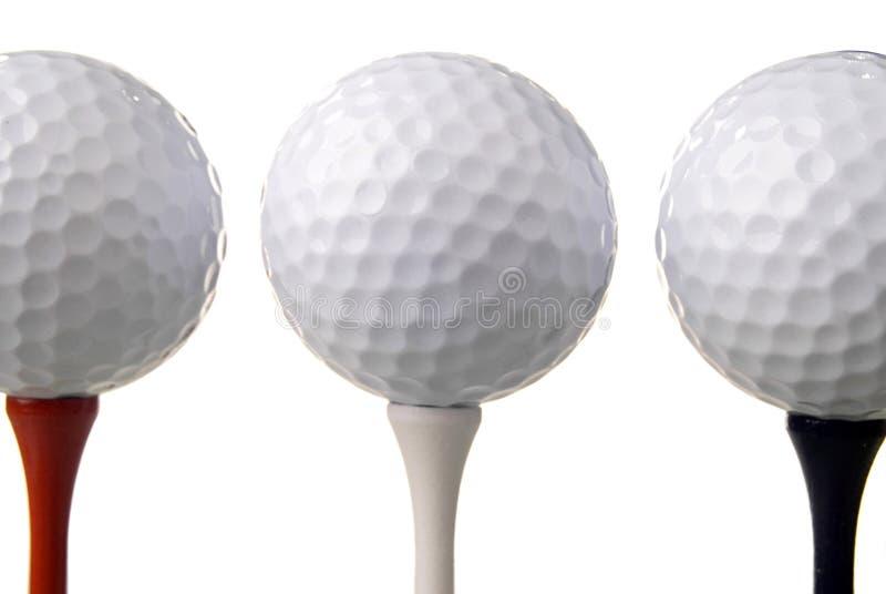 Three golf balls on tees stock photos