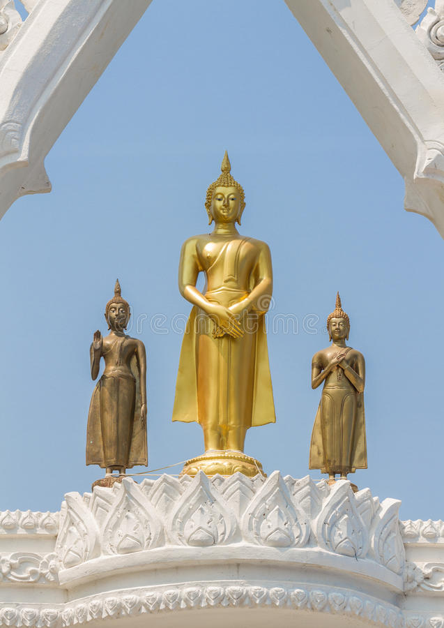 Three graceful and peaceful golden Buddha statues standing under beautiful white arch with blue sky background. Composition with perfect balance and symmetry stock images