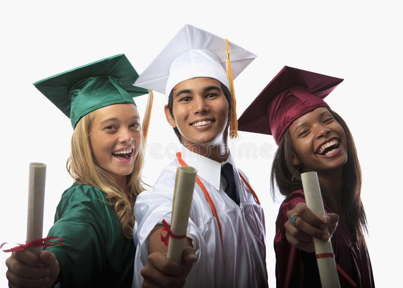 Three graduates in cap and gown. With diplomas royalty free stock photography