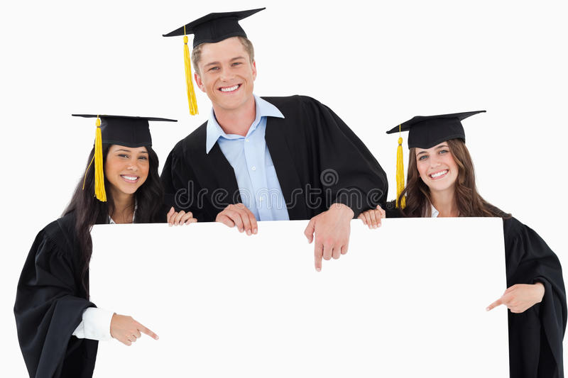 Three graduates pointing to the blank sign. As they look at the camera royalty free stock photo