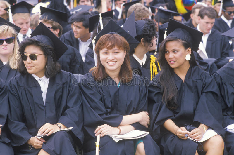 Three graduates smiling during their ceremony royalty free stock image