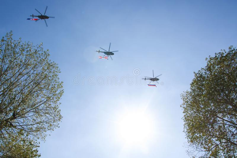 Three gray military helicopters fly in the blue sky. They carry flags with them. Demonstration of a peaceful flight. Day of the royalty free stock photos