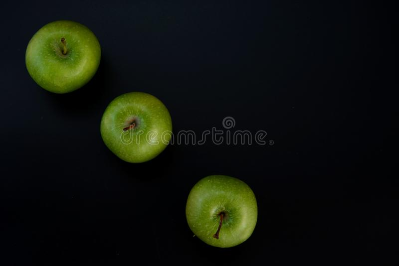 Three green apples on a black background. The insulation on the black. stock photo