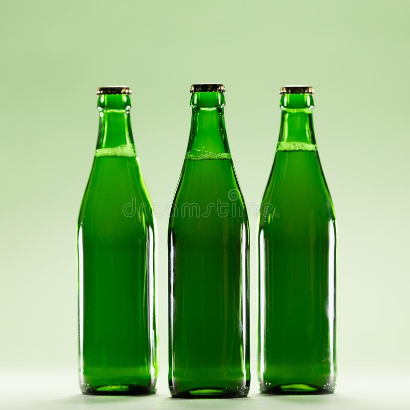 Three green bottles on a light green background. Craft beers. St Patrick`s Day. Irish culture royalty free stock images