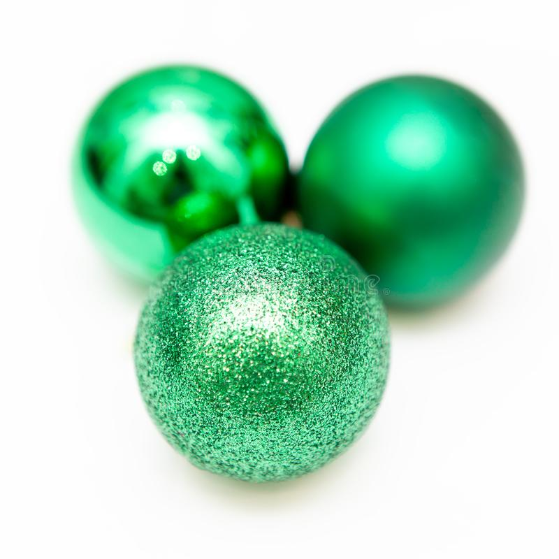 Three green christmas toys, decoration. Glitter. Isolated on white background stock image
